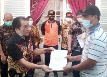 KETERANGAN SEHAT: Bupati Budhi Sarwono menyerahkan surat keterangan sehat kepada pasien Covid-19 yang dinyatakan sembuh dari hasil uji swab evaluasi, Jumat (26/6). (SB/Castro Suwito-2)