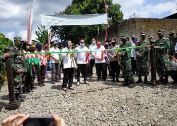 JALAN BARU: Bupati Tiwi melakukan pemotongan pita pembukaan jalan baru saat penutupan TMMD Sengkuyung di Desa Patemon.  (SB/Arief Noegroho)
