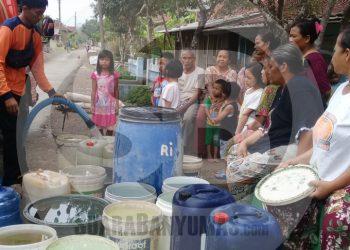 TERIMA BANTUAN: Warga Dusun Gunungtelu, Desa Gunungtelu, Kecamatan Karangpucung, Kabupaten Cilacap menerima bantuan air bersih dari BPBD bersama pihak terkait, kemarau tahun lalu. (SB/Teguh Hidayat Akbar)