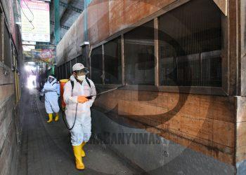 SEMPROT DISINFEKTAN: Petugas melakukan penyemprotan disinfektan di area sekitar Pasar Wage Purwokerto yang ditutup sementara akibat ditemukannya 5 kasus positif COVID-19 di pasar tersebut, Selasa (14/7) (SB/Dian Aprilianingrum-2)