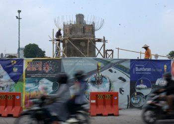 PEMBANGUNAN TUGU: Pengendara melintas di dekat Tugu Gada Rujakpolo yang sedang dibangun di pintu masuk underpass Purwokerto, Senin (10/8). (SB/Dian Aprilianingrum)