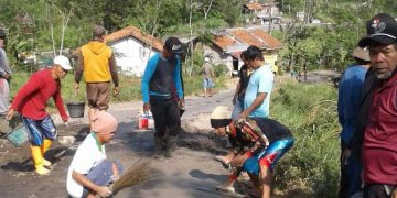 KERJA BAKTI: Warga dan personel Ansor Banser Desa Krajan, Kecamatan Pekuncen memperbaiki jalan di perbatasan Brebes-Banyumas Jumat (7/8) pagi.