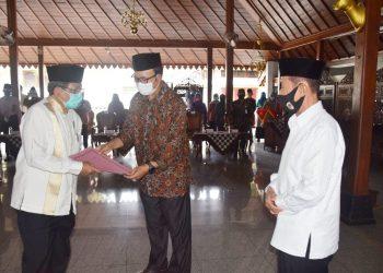 SERAHKAN SK PENGURUS: Bupati Achmad Husein menyerahkan surat keputusan kepengurusan MUI Kabupaten Banyumas masa bakti 2020-2025, diketuai KH Taefur Arofat, di Pendapa Sipanji Purwokerto, Jumat (11/9).