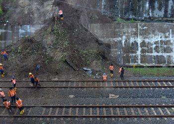 BERSIHKAN LONGSOR: Pekerja membersihkan tanah longsor yang menimbun rel ganda kereta api di dekat terowongan Kebasen, Banyumas, Kamis (29/10) (SB/Dian A)