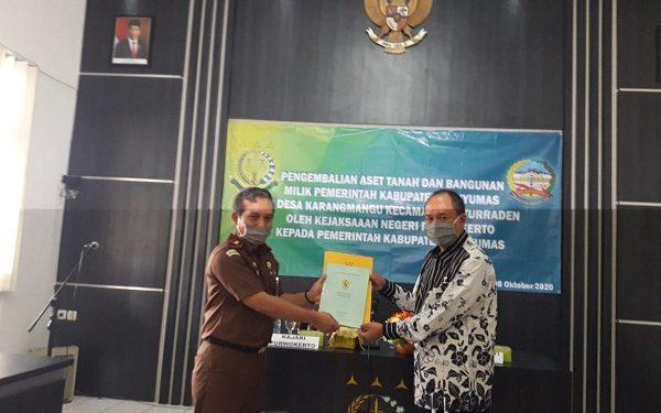 BUKTI SERTIFIKAT : Kepala Kejaksaan Negeri Purwokerto, Sunarwan  menyerahkan kembali bukti sertifikat kepemilikan aset milik Pemkab di Desa  Karangmangu Baturraden, Kamis (8/10). (SB/Agus Wahyudi)